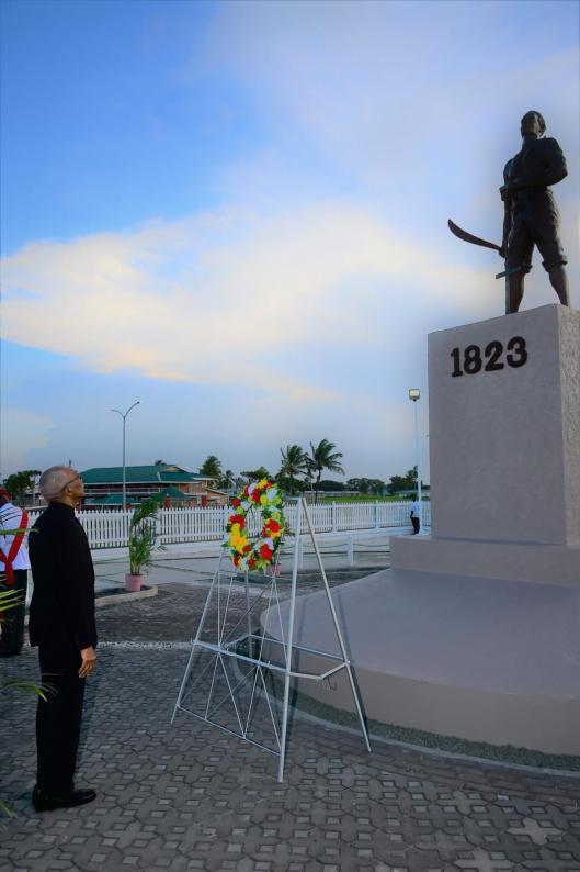 President David Granger places a wreath at the 1823 Demerara Revolt Monument at Atlantic Avenue