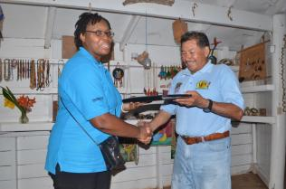 A member from the Barbados team presents a small token to Minister of Indigenous Peoples' Affairs, Sydney Allicock