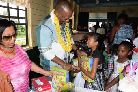 Minister of State, Joseph Harmon distributing gifts to the children