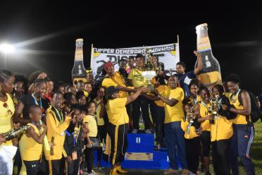 The Upper Demerara/Kwakwani team is all smiles as they receive their championship trophy