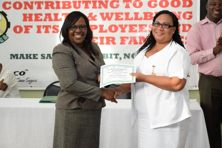 Minister within the Ministry of Public Health, Dr. Karen Cummings presenting one of the graduates, Sabrina Brummel with her certificate