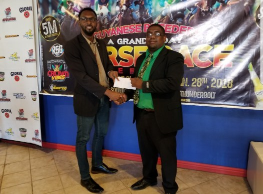 Director of Sport Christopher Jones presenting the National Sports Commission's contribution to Steven Cheefoon, co-founder Caribbean Nations Group