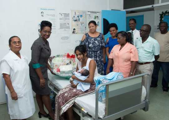 Hollis Kellman, Republic Bank representative hands over another hamper put together by RBL for the baby