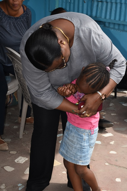 Minister Broomes comforting one of the children affected by the fire