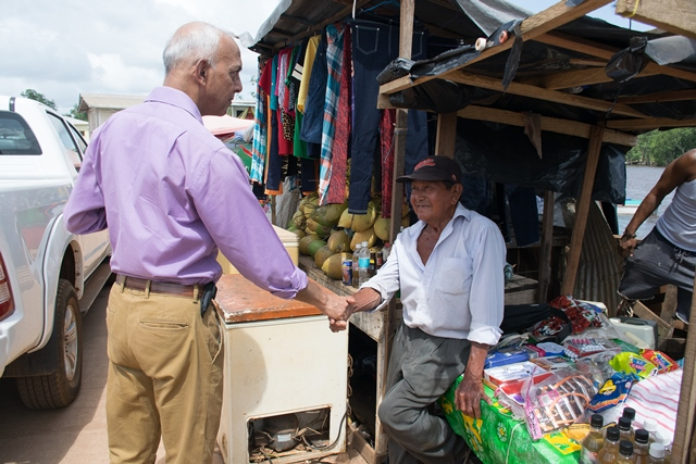 Minister of Communities Ronald Bulkan interacts with a vendor in Kumaka, Mabaruma on Friday