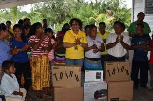 Minister within the Ministry of Indigenous Peoples' Affairs Valerie Garrido-Lowe (left) presenting equipment to CDC Chairperson Sherwin Lewis of Smith Creek and HEYS participants
