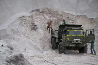 Men loading sand into truck while in the face of the sand wall