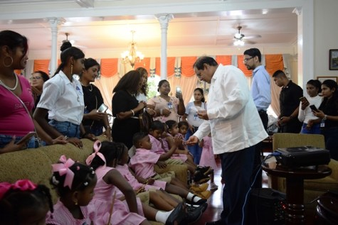 Prime Minister, Hon. Moses Nagamootoo shares small tokens to students of the Little Angels Play Group.