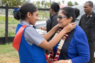 Mrs. Sita Nagamootoo is garlanded by a student of Alness Primary School