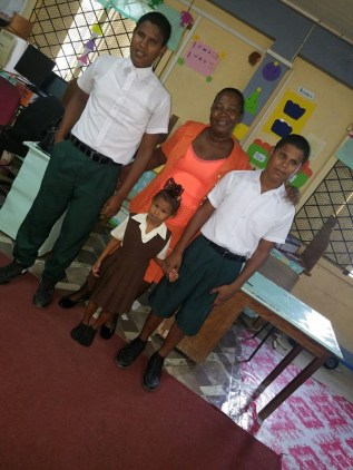 Teacher Shellon waving with Relon and Roell Sumner and their little sister Jangi