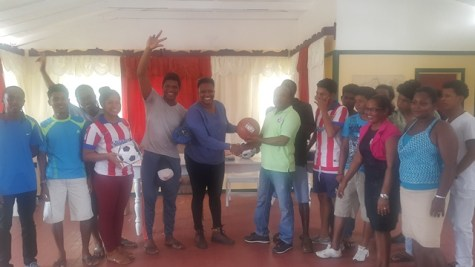 Minister within the Ministry of Public Infrastructure, Annette Ferguson donating the sport gear to the sport club.
