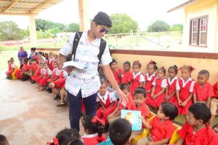 One of Prime Minister Nagamootoo and Mrs. Nagamootoo's grandsons distributes reading material to students of the Arapaima Nursery School.