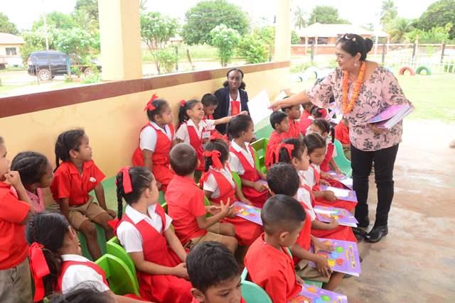 Mrs. Nagamootoo distributing presents to students of the Arapaima Nursery School.