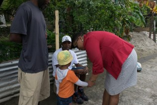 Hon. Volda Lawrence with young child, listening to the plea of residents.