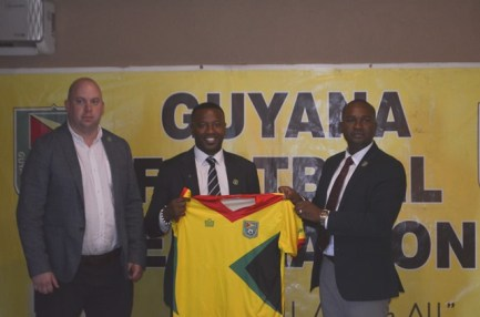 Newly appointed Head Coach Michael Johnson (center) with GFF President Wayne Forde (right) and GFF Technical Director Ian Greenwood (left).