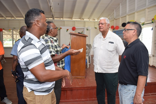 Agriculture Minister, Noel Holder and Chief Fisheries Officer, Denzil Roberts being engaged by fishermen.