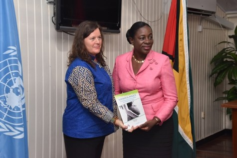 UNICEF representative to Guyana and Suriname, Sylvie Fount handing over the policy to Minister of Education, Nicolette Henry.