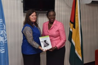 United Nations International Children's Emergency Fund (UNICEF) Representative, Ms. Sylvie Fouet hands over the National Policy for the Reintegration of Adolescent Mothers into the Formal Education System to Minister of Education, Ms. Nicolette Henry.