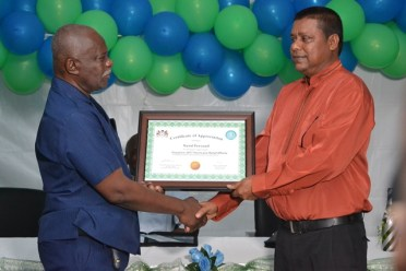Minister of Citizenship, Winston Felix hands over the award of appreciation to Nand Persaud.