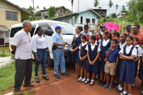 Minister of Indigenous Peoples' Affairs, Sydney Allicock handing over the keys to the bus to Thomas Hills, Community Development Council (CDC) Chairperson, Vicky Cheung in the presence of the students