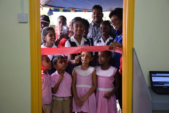 Minister of Public Telecommunications, Catherine Hughes smiles as a pupil of Cumberland Primary cuts the ribbon.