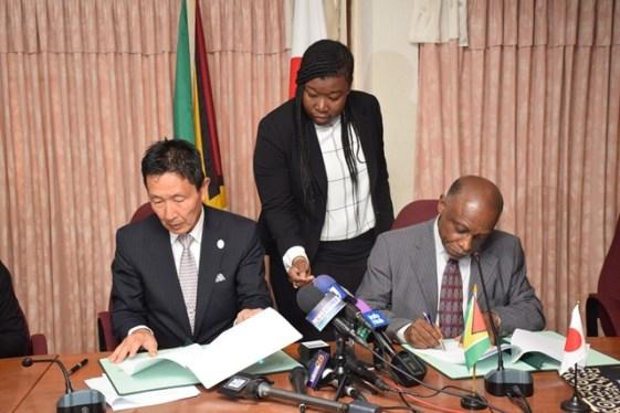 Minister of Foreign Affairs, Carl Greenidge [right] and Ambassador of Japan to Guyana, Mitsuhiko Okada [left] signing the grants.