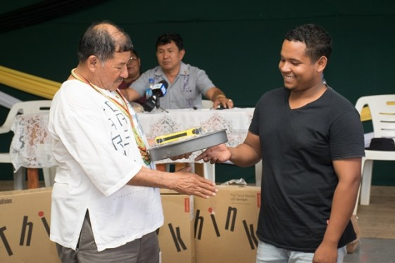 Minister of Indigenous Peoples' Affairs, Sydney Allicock handing over equipment to one of the young entrepreneurs.