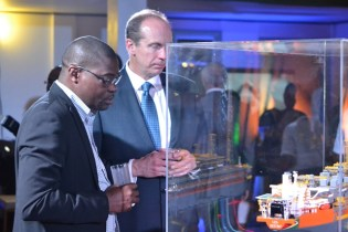Minister of Public Infrastructure, David Patterson, and another attendee examining the replica of the Liza Destiny FPSO.