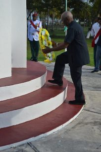 Minister within the Ministry of Social Protection Keith Scott laying a wreath at the Enmore Martyrs monument