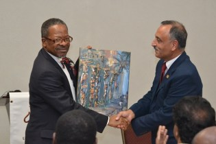 Professor Al-Zubaidy receiving a painting from the UG Vice Chancellor, Ivelaw Griffith.