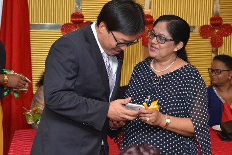 A member of the 13th Chinese Medical Brigade receives a token of appreciation from Mrs. Sita Nagamootoo.