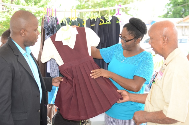 Director of Community Development, Ernest Elliot, (right) viewing exhibits with Technical Officer within the Ministry of Communities, Shawn Austin along with a Blueberry Hill CDC member.