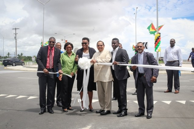 Minister within the Ministry of Public Infrastructure, Annette Ferguson surrounded by Minister of Public Infrastructure, David Patterson [front left] and Prime Minister, Moses Nagamootoo [third right] as Minister Ferguson cuts the ribbon to officially open the roundabout.