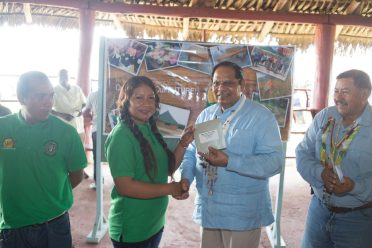Prime Minister and Acting President, Moses Nagamootoo handing over the money to Joan Thomas, young entrepreneur of Quarries Village in the presence of Minister of Indigenous Peoples' Affairs, Sydney Allicock