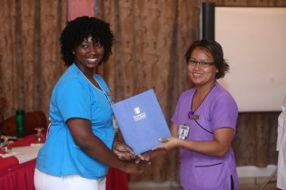 One of the Critical Care Nurses, Tiffany Blair receives her certificate from her preceptor at the graduation.