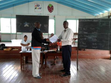 Regional Vice Chairman Elroy Adolph presenting the Toshao of Kimbia with official documentation after the elections.