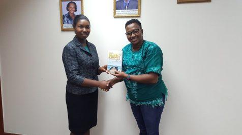 Author Feigel Niles presents a copy of her novel to Minster Annette Ferguson
