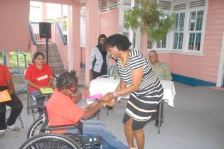 One of the participants receiving her prize from Hyacinth Massay, Rehabilitation Officer.
