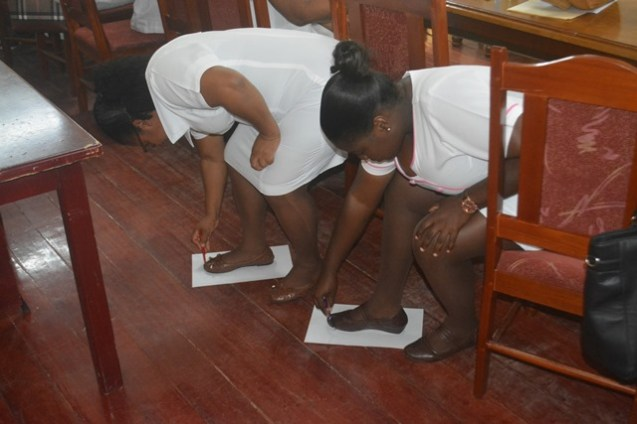 Participants examining their feet during the workshop.