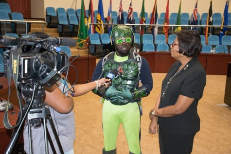 Agri-Man, [centre, in costume] explains his character to DPI's Communications Officer, Delicia Haynes and Minister of Public Telecommunications, Catherine Hughes