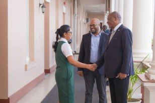 DPI's Director for the day, Devika Rajaram greets Minister of State, Joseph Harmon.