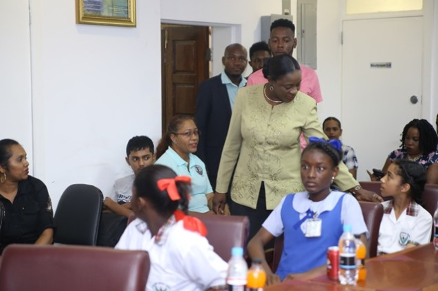 Minister of Education, Nicolette Henry engaging one of the students as she makes her way into the ministry's boardroom