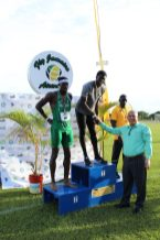 Minister of Social Cohesion Dr. George Norton congratulating Kirani James after winning the 400m race