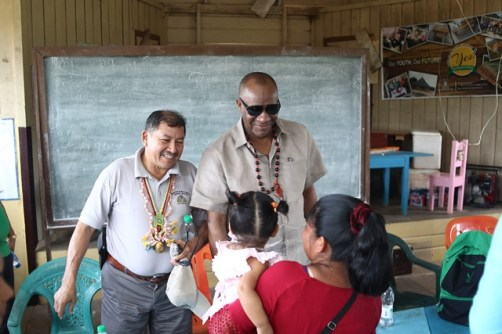 Minister of State, Joseph Harmon and Minister of Indigenous Peoples' Affairs, Sydney Allicock sharing a light moment with a mother and her child.