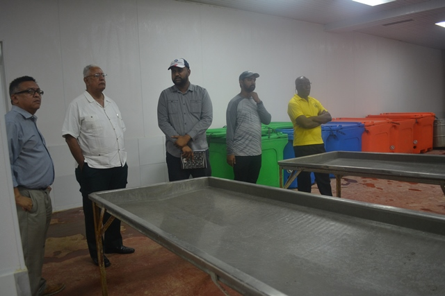 Minister Holder and other officials while touring Gopie Investments Inc's shimp processing facility.