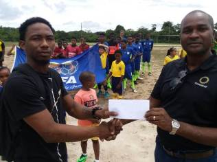 Shaquille Hopkins representing Mil Ballers FC receiving the Winning Cheque from GFF President Wayne Forde.