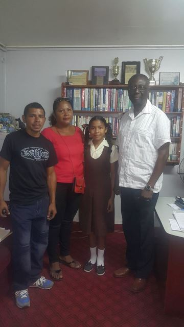 [left to right] Marlon Fredericks, Donette Edwards, Anasie Fredericks and Regional Executive Officer (REO), Rupert Hopkinson posing with the top hinterland student.