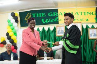 Permanent Secretary, Delma Nedd presents Joel Halley with his certificate