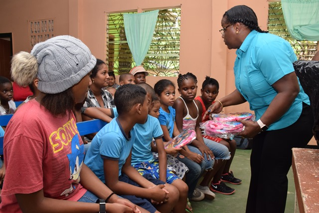 Minister within the Ministry of Natural Resources, Simona Broomes distributing school supplies to young Victory Valley residents.