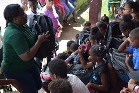 Minister within the Ministry of Natural Resources, Simona Broomes distributing school supplies to students of Bartica.